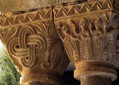 Abad entre el diaca i el sots-diaca. Capitell ubicat a la galeria sud del claustre del monestir de l'Estany
