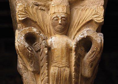 Noia entre dues palmetes derivades en caps de llebrer. Capitell ubicat a la galeria est del claustre del monestir de l'Estany
